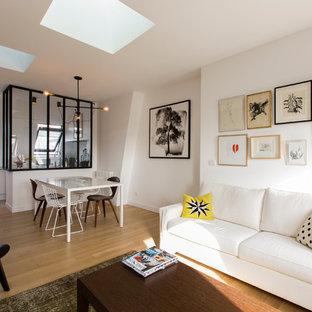 Cette photo montre un salon scandinave ouvert avec un mur blanc et un sol en bois clair.