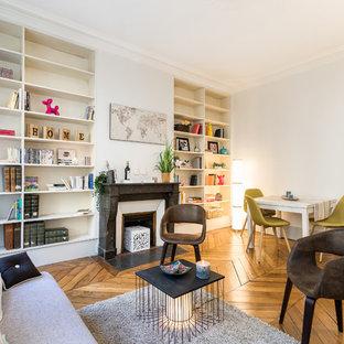 Inspiration pour un salon design ouvert avec une salle de réception, un mur blanc, un sol en bois brun, une cheminée standard, aucun téléviseur et un sol marron.