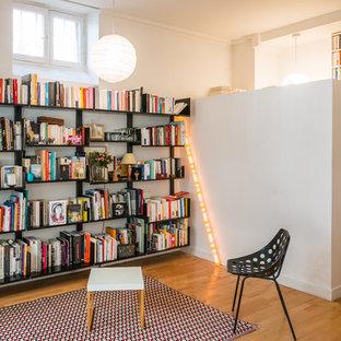 Exemple d'un salon avec une bibliothèque ou un coin lecture tendance de taille moyenne avec un mur blanc, un sol en bois brun, aucune cheminée et aucun téléviseur.
