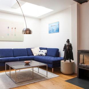 Inspiration pour un salon design ouvert avec un mur blanc, un sol en bois brun, un poêle à bois et un sol marron.
