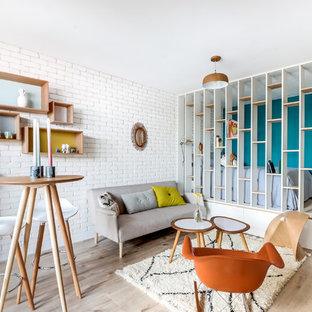 Cette image montre un salon nordique de taille moyenne et ouvert avec un mur blanc, aucune cheminée, aucun téléviseur et un sol en bois clair.
