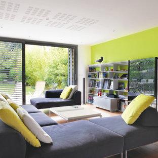 Exemple d'un grand salon avec une bibliothèque ou un coin lecture tendance fermé avec un sol en bois brun, aucune cheminée et aucun téléviseur.