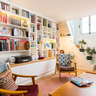Exemple d'un salon avec une bibliothèque ou un coin lecture scandinave ouvert et de taille moyenne avec un mur blanc, un sol en bois brun, aucune cheminée et aucun téléviseur.
