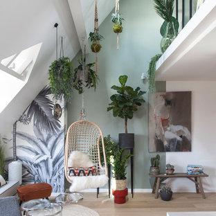 Offenes Modernes Wohnzimmer mit grüner Wandfarbe, hellem Holzboden und beigem Boden in Paris
