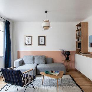 Aménagement d'un salon contemporain ouvert avec un mur rose, un sol en bois brun et un sol marron.