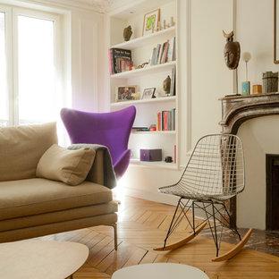 Idée de décoration pour un salon avec une bibliothèque ou un coin lecture nordique de taille moyenne et fermé avec un mur blanc, un sol en bois brun, une cheminée standard, aucun téléviseur et un manteau de cheminée en pierre.
