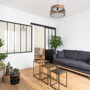 Exemple d'un salon scandinave fermé avec une salle de réception, un mur blanc, un sol en bois clair et un sol beige.