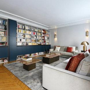 Exemple d'un salon tendance fermé avec une salle de réception, un mur gris, un sol en bois clair, un sol beige et un téléviseur dissimulé.