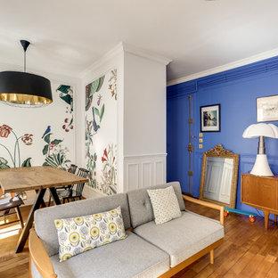 Inspiration pour un salon bohème ouvert avec un mur multicolore et un sol en bois brun.