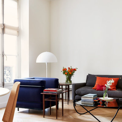 Example of a danish light wood floor living room design in Paris with white walls