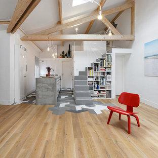 Cette image montre un grand salon avec une bibliothèque ou un coin lecture design avec un mur blanc, un sol en bois brun, aucune cheminée et aucun téléviseur.