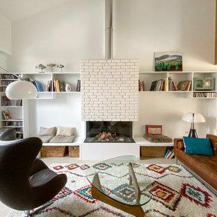 Exemple d'un salon tendance ouvert avec un mur blanc, une cheminée standard, un manteau de cheminée en brique, un sol gris et un plafond voûté.
