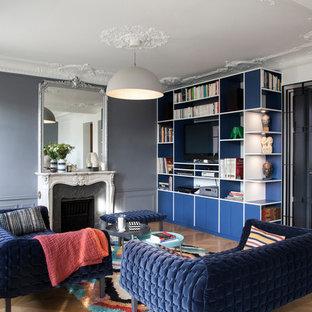 Aménagement d'un salon classique avec un mur gris, un sol en bois brun, une cheminée standard et un sol marron.