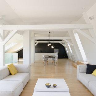 Cette photo montre un salon mansardé ou avec mezzanine scandinave avec un mur blanc et un sol en bois clair.