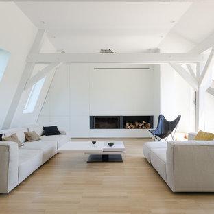 Réalisation d'un salon nordique avec un mur blanc, un sol en bois clair, aucune cheminée et aucun téléviseur.
