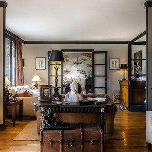 Réalisation d'un grand salon tradition ouvert avec un sol en bois clair, un mur marron, aucune cheminée et aucun téléviseur.
