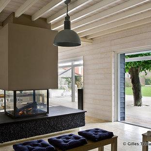 Idee per un grande soggiorno boho chic aperto con pareti beige, pavimento in pietra calcarea, cornice del camino in pietra, nessuna TV, camino sospeso e pavimento beige