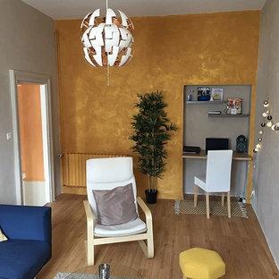 Diseño de salón cerrado, nórdico, pequeño, sin chimenea, con paredes amarillas, suelo de madera clara y televisor colgado en la pared