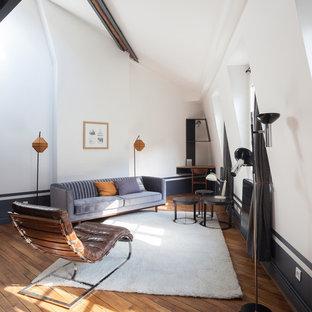 Réalisation d'un salon mansardé ou avec mezzanine nordique de taille moyenne avec un sol en bois brun, aucune cheminée, un mur bleu et aucun téléviseur.