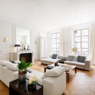 Réalisation d'un salon design fermé avec une salle de réception, un mur blanc, un sol en bois clair et une cheminée standard.
