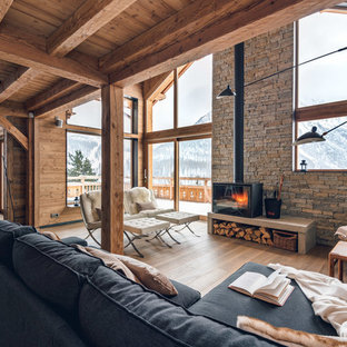 Inspiration pour un salon avec une bibliothèque ou un coin lecture chalet de taille moyenne et ouvert avec un sol en bois clair, un poêle à bois, aucun téléviseur et un mur marron.