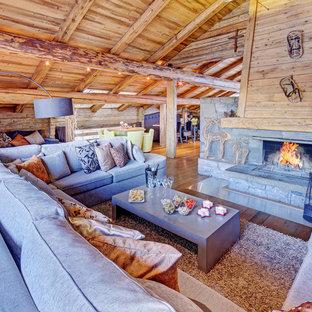 Idée de décoration pour un grand salon chalet avec un sol en bois brun, une cheminée standard, un manteau de cheminée en pierre, une salle de réception, un mur marron et aucun téléviseur.