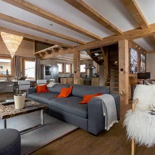 Réalisation d'un salon chalet ouvert et de taille moyenne avec un mur beige, un sol en bois brun, aucun téléviseur et aucune cheminée.