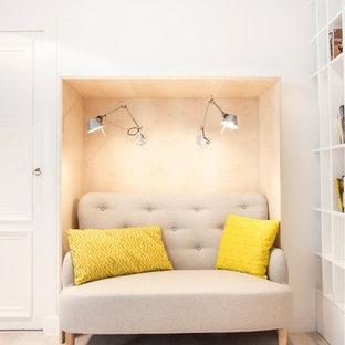 Idées déco pour un petit salon avec une bibliothèque ou un coin lecture classique avec un mur blanc et un sol en bois clair.