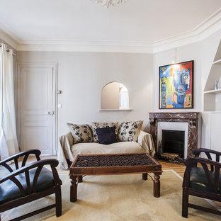 Cette image montre un grand salon avec une bibliothèque ou un coin lecture design fermé avec un mur beige, un sol en bois brun, une cheminée d'angle, un manteau de cheminée en pierre et un téléviseur indépendant.