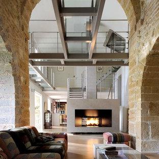 Réalisation d'un grand salon urbain ouvert avec une cheminée double-face, un mur beige, un sol en carrelage de céramique et aucun téléviseur.