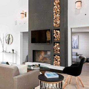 Aménagement d'un salon contemporain avec un mur blanc, un sol en bois clair, une cheminée double-face, un téléviseur fixé au mur et un sol beige.
