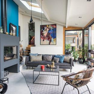 パリのエクレクティックスタイルのおしゃれなリビング (青い壁、コンクリートの床、標準型暖炉、グレーの床) の写真