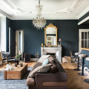 Idée de décoration pour un grand salon bohème ouvert avec un bar de salon, une cheminée standard, un manteau de cheminée en pierre, un téléviseur dissimulé, un sol marron, un mur bleu et un sol en bois brun.