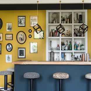 Esempio di un soggiorno bohémian di medie dimensioni e aperto con angolo bar, pareti gialle, parquet chiaro, camino classico, cornice del camino in pietra, TV nascosta e pavimento beige