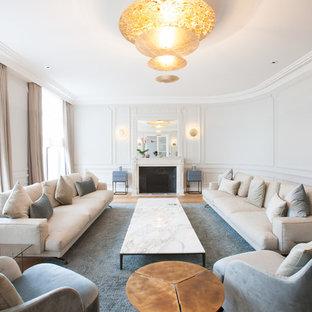 Modelo de salón para visitas cerrado, tradicional renovado, extra grande, sin televisor, con suelo de madera en tonos medios, chimenea tradicional, paredes blancas y marco de chimenea de piedra