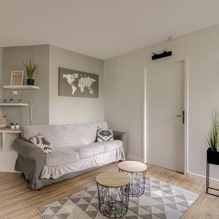 Cette image montre un salon nordique avec une salle de réception, un mur blanc, un sol en bois brun et un sol marron.