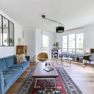 Idées déco pour un salon rétro ouvert et de taille moyenne avec un mur blanc, un sol en bois clair, aucune cheminée, un téléviseur indépendant et un sol marron.