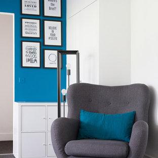Esempio di un piccolo soggiorno industriale aperto con libreria, pareti blu, moquette, nessun camino, nessuna TV e pavimento nero