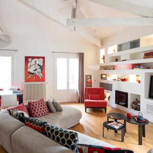 Réalisation d'un salon design ouvert avec un mur blanc, un sol en bois brun, une cheminée standard, un manteau de cheminée en métal, un téléviseur indépendant et un sol marron.