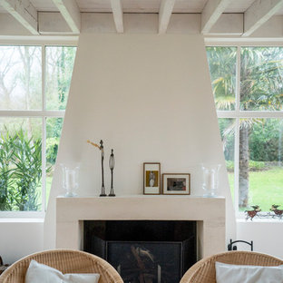 This is an example of a nautical living room in Rennes with white walls, terracotta flooring, a standard fireplace, a stone fireplace surround and pink floors.