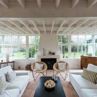 Idées déco pour un salon bord de mer avec un mur blanc, un sol en carreau de terre cuite, une cheminée standard, un manteau de cheminée en pierre et un sol beige.