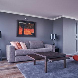 Cette photo montre un salon tendance de taille moyenne et fermé avec un mur gris, un sol en bois brun, aucune cheminée et aucun téléviseur.