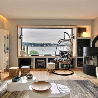 Cette photo montre un salon tendance avec un mur gris, un sol en bois brun, un poêle à bois, un téléviseur indépendant et un sol marron.