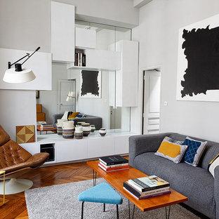 Cette photo montre un salon tendance fermé avec un mur gris et un sol en bois brun.