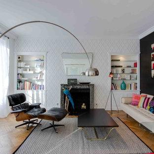 Aménagement d'un salon avec une bibliothèque ou un coin lecture contemporain de taille moyenne et ouvert avec un mur blanc, un sol en bois brun, une cheminée standard, un manteau de cheminée en pierre et aucun téléviseur.