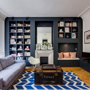 Idée de décoration pour un salon design fermé avec un mur noir, un sol en bois brun, une cheminée standard, un téléviseur indépendant, un sol marron et une salle de réception.