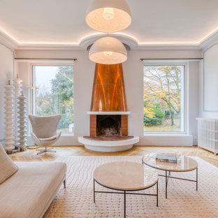 Réalisation d'un très grand salon design fermé avec un mur bleu, un sol en bois brun, une cheminée standard, un manteau de cheminée en métal et un téléviseur indépendant.