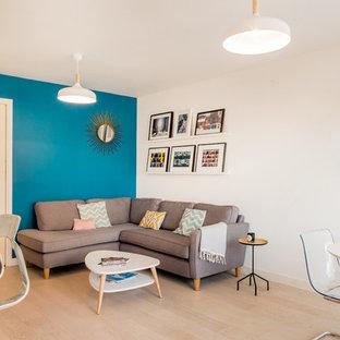 Cette image montre un salon design de taille moyenne et ouvert avec un mur bleu, un sol en bois clair, aucune cheminée, une salle de réception et aucun téléviseur.