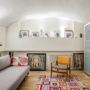 Cette image montre un salon design de taille moyenne et fermé avec un mur blanc, un sol en bois clair, aucune cheminée et aucun téléviseur.
