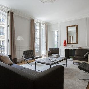 Cette image montre un grand salon design ouvert avec une salle de réception, un sol en bois brun, une cheminée standard, un manteau de cheminée en pierre et aucun téléviseur.